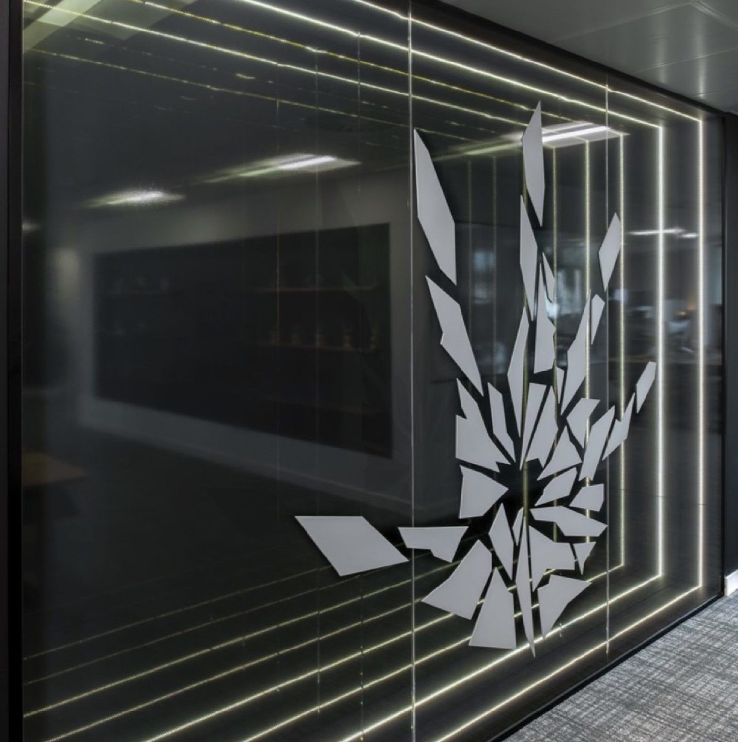 EA Frostbite logo on layered glass wall with hand print